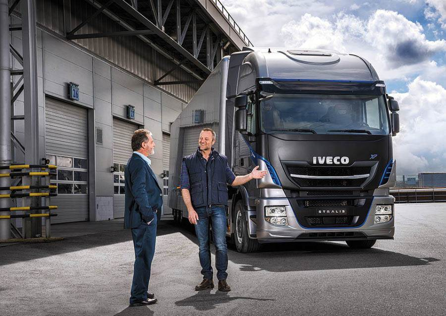 Two men stood before an Iveco Stralis